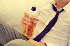 Young man drinking alcohol from a bottle Royalty Free Stock Images