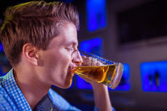 Young man drinking beer Stock Images