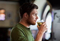 Young man drinking beer at bar or pub Royalty Free Stock Images