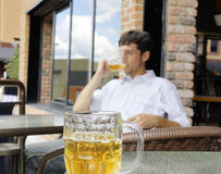 Young man drinking beer. Focus on front glass bock Stock Photo