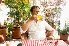 Young man drinking beer at hot day on restaurant summer terrace Royalty Free Stock Images