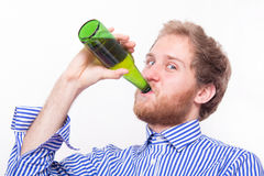 Young man drinking a bottle of beer Royalty Free Stock Images