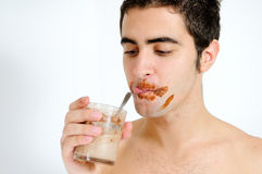 Young man drinking chocolate milkshake. A boy with the dirty mouth drinking chocolate milkshake Royalty Free Stock Photos