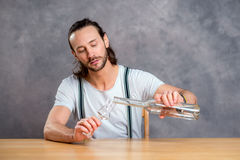 Young man drinking clear spirit Stock Images