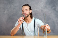Young man drinking clear spirit Royalty Free Stock Photos