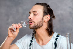 Young man drinking clear spirit Stock Photos