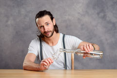 Young man drinking clear spirit Stock Image