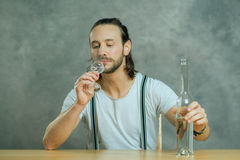 Young man drinking clear spirit Royalty Free Stock Image