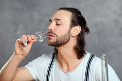 Young man drinking clear spirit Stock Photo