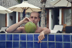 Young man drinking a cocktail of coconut Stock Photos