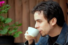 Young Man Drinking Coffee. A young man having a cup of coffee at restaurant's terrace Stock Photo