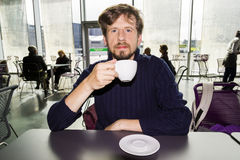 Young man drinking coffee in a cafe. Man drinking coffee a cafe Royalty Free Stock Photography