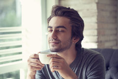 Young man drinking coffee in cafe Royalty Free Stock Photography