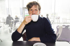 Young man drinking coffee in a cafe Stock Images