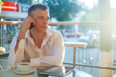 Young man drinking coffee in cafe and using phone. Stock Photography