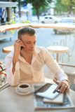 Young man drinking coffee in cafe and using phone. Stock Images