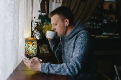 Young man drinking coffee in cafe and using phone. Handsome Man Royalty Free Stock Photos