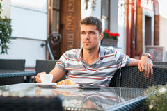 Young man drinking coffee with croissant. Breakfast Stock Image