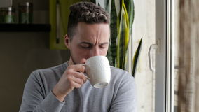 Young man drinking coffee and enjoying view from the window stock footage