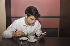 Young Man Drinking Coffee While Looking at Mobile Phone Royalty Free Stock Image