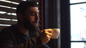 Young man drinking coffee next to the window in the cafe. A man with a beard stock footage