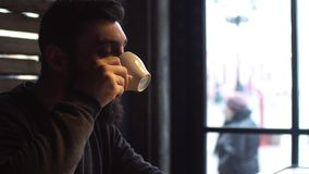 Young man drinking coffee next to the window in the cafe. A man with a beard. stock footage