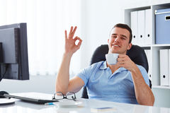 Young man drinking coffee in the office Stock Photos