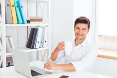 Young man drinking coffee in office and looking at camera Royalty Free Stock Photos
