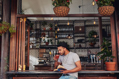 Young man drinking coffee and reading book Royalty Free Stock Photos