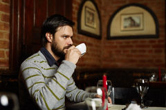Young man drinking coffee in a restaurant Stock Images