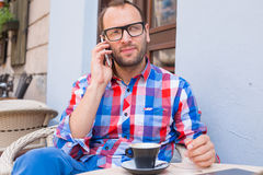 Young man drinking coffee in restaurant. He is holding a mobile phone. Royalty Free Stock Image