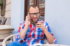 Young man drinking coffee in restaurant. He is holding a mobile phone. Royalty Free Stock Photo