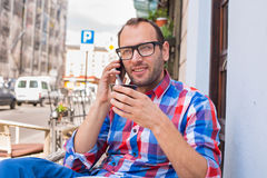 Young man drinking coffee in restaurant. He is holding a mobile phone. Stock Images