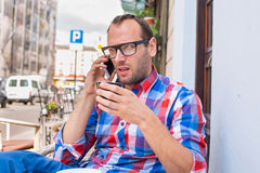 Young man drinking coffee in restaurant. He is holding a mobile phone. Royalty Free Stock Photography
