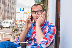 Young man drinking coffee in restaurant. He is holding a mobile phone. Stock Photos