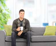 Young man drinking coffee seated on couch at home. Shot with tilt and shift lens Stock Images
