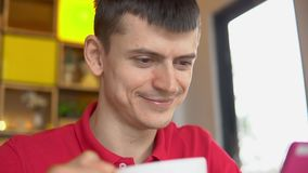 Young man drinking coffee and sending messages with his mobile phone. In cafe stock video footage