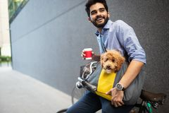 Young man drinking coffee while sitting on his bicycle with dog outdoors. Young bearded man drinking coffee while sitting on his bicycle with dog outdoors royalty free stock image