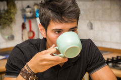 Young Man Drinking Coffee Sitting at Kitchen Table Royalty Free Stock Images