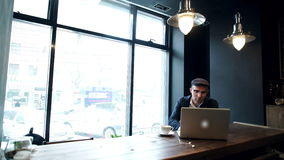 Young man drinking coffee on the street while using tablet computer stock footage