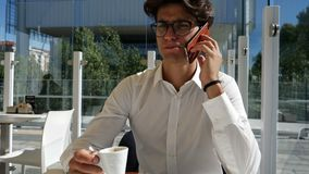 Young man drinking coffee and talking on phone stock video