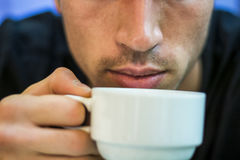 Young man drinking coffee or tea Stock Photography