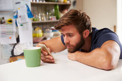 Young Man Drinking Coffee And Using Mobile Phone At Home Royalty Free Stock Image