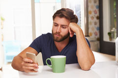 Young Man Drinking Coffee And Using Mobile Phone At Home Stock Photography
