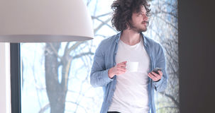 Young man drinking coffee and using a mobile phone at home stock images
