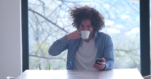 Young man drinking coffee and using a mobile phone at home royalty free stock photo