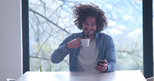 Young man drinking coffee and using a mobile phone at home stock photos