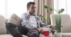 Young man drinking coffee and watching tv at home. Relaxed african american man drinking coffee and watching tv at home stock video footage