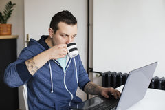 Young man drinking coffee and working Royalty Free Stock Images