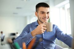 Young man drinking coffee while working stock photo